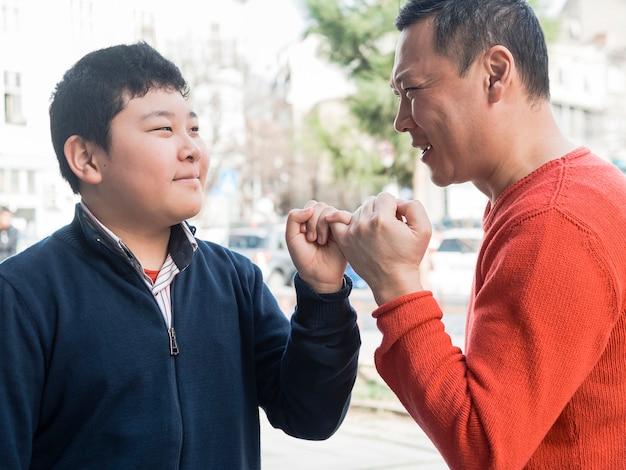Asiático pai e filho segurando os dedinhos