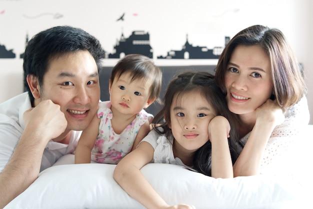 Asiático pai, mãe, irmã mais velha e bebê jovem deitado na cama no quarto com um sorriso.
