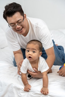 Asiático pai tocando e brincando com o bebê menino na cama na casa