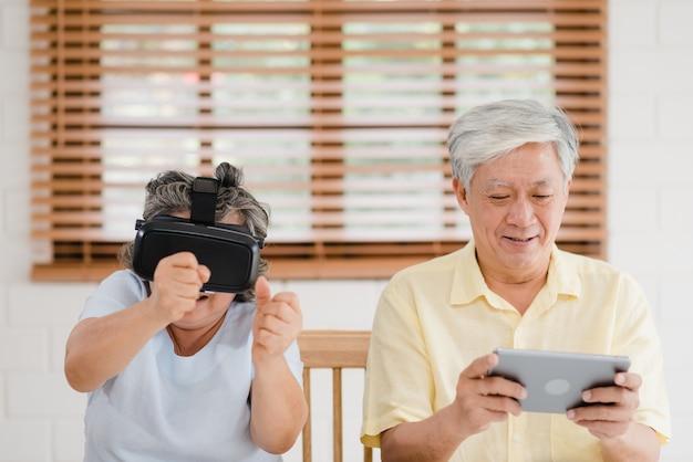 Asiático, par ancião, usando, tabuleta, e, virtual, realidade, simulador, jogos jogos, em, sala de estar