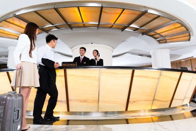 Asiático, par chinês, chegando, em, hotel, escrivaninha dianteira
