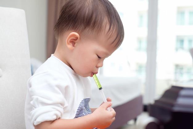 Asiático pequeno bonito 2 anos de idade criança bebê menino que está com gripe, alimentando-se com remédio líquido com uma seringa, conceitos de resfriado e gripe de febre. foco seletivo na medicina & seringa