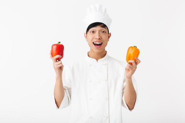 Asiático positivo chefe homem com uniforme branco de cozinheiro, sorrindo para a câmera enquanto segura papéis doces, vegetais isolados sobre a parede branca