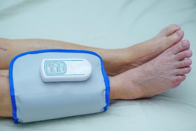 Asiático, sênior, ou, idoso, mulher velha, paciente, com, cordless, compressa ar, pressão, perna, massa