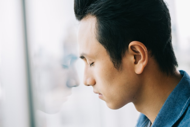 Asiático triste na janela