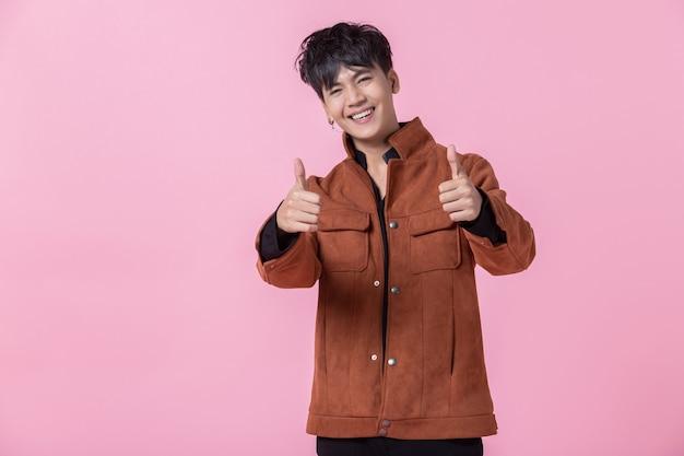 Asiático um homem jovem e bonito apontando com as duas mãos mostrando os polegares para cima