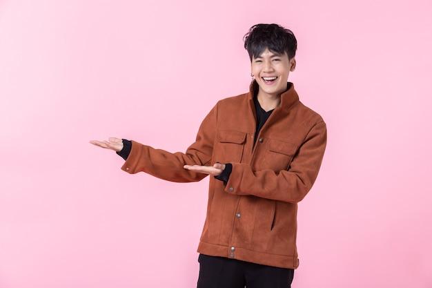 Asiático, um homem jovem e bonito apontando com duas mãos e dedos