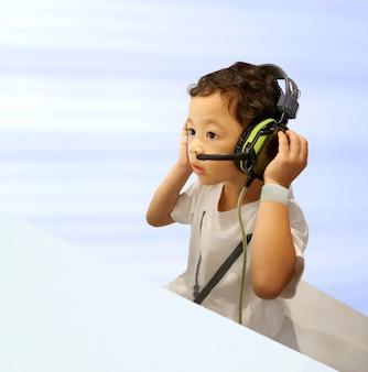 Asiático um menino bonitinho usando fone de ouvido, ouvindo música incrível ou entretenimento animado