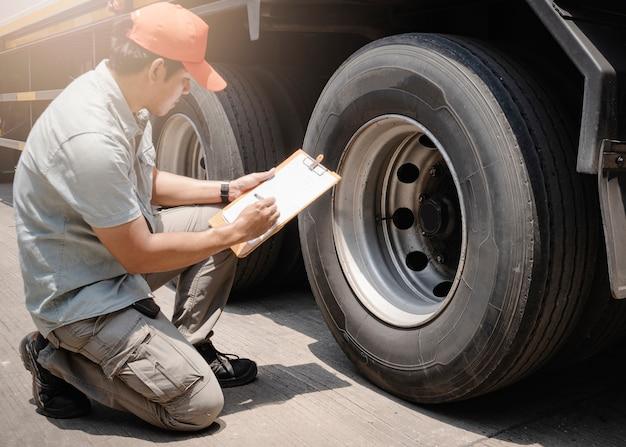 Asiático, um motorista de caminhão segurando uma prancheta está verificando a segurança das rodas e pneus de um caminhão.