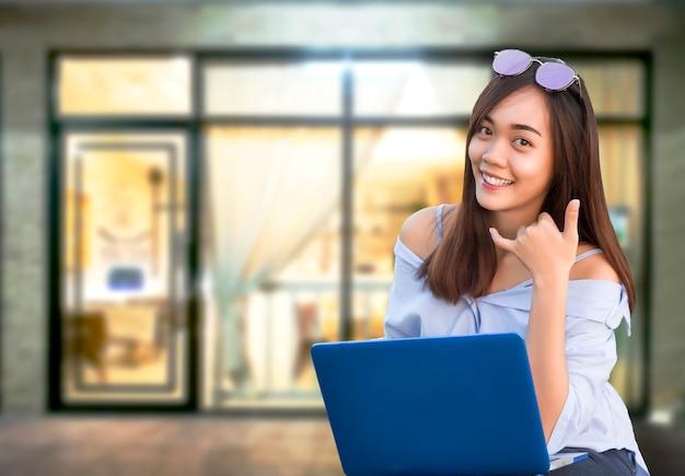 Asiático usa símbolo de chamada de laptop em negócios lanudry