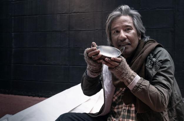 Asiático vagabundo se sentir feliz com o leite doado, sem-teto e faminto vagabundo segurando uma xícara de leite