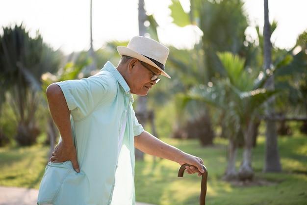 Asiático velho andando no parque e tendo uma dor nas costas, dor nas costas.
