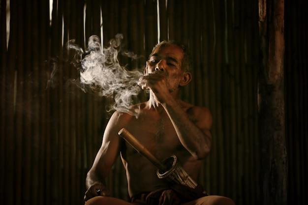 Asiático velho fumando cigarro e a fumaça liberada pela boca contra o escuro