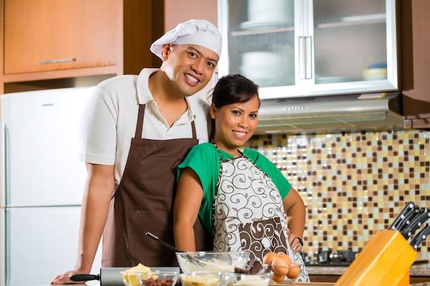 Asiatisches paar beim kuchen backen em küche