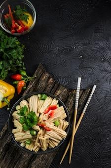 Aspargo marinado em coreano em uma tigela preta com pauzinhos em um fundo escuro, vista superior flatlay.