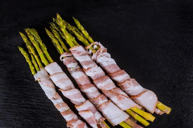 Aspargo orgânico fresco envolvido com bacon em uma opinião superior da placa de corte