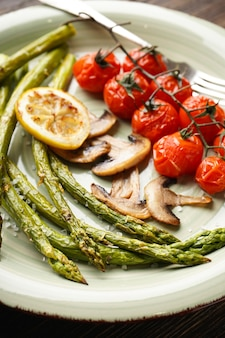 Aspargos cozidos e tomate cereja em um prato. fechar-se.