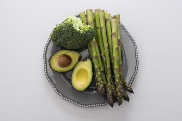Aspargos frescos, abacate e brócolis em um prato