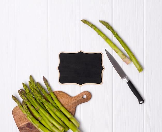 Aspargos verdes frescos na tábua com faca na mesa da mesa de madeira branca