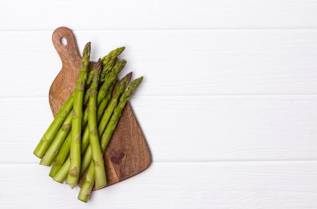 Aspargos verdes frescos na tábua na mesa de madeira branca