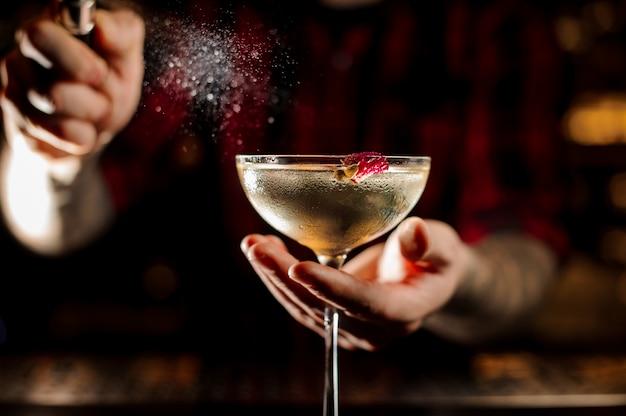Aspersão de mixologist amarga no copo de cocktail elegante