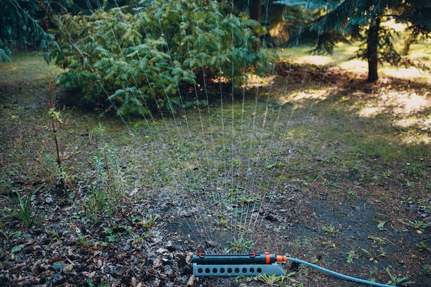 Aspersor de gramado espirrando água sobre a grama verde no parque do jardim. sistema de irrigação.