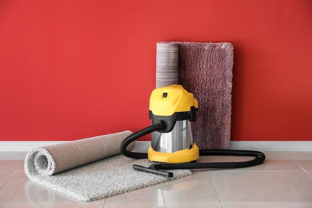 Aspirador de pó com tapetes macios perto da parede colorida