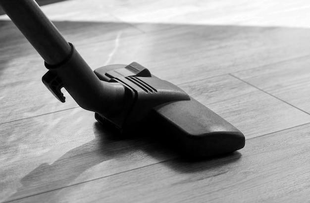 Aspirador de pó em um piso de madeira, close-up. conceito de serviço de limpeza