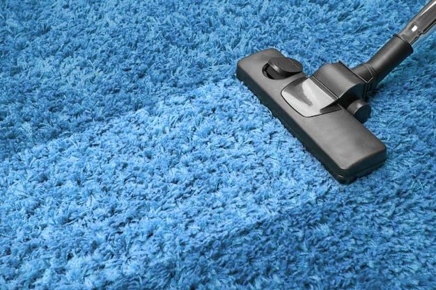 Aspirador de pó no tapete azul
