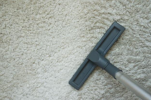 Aspirador de pó no tapete de lã. conceito de limpeza de casa.