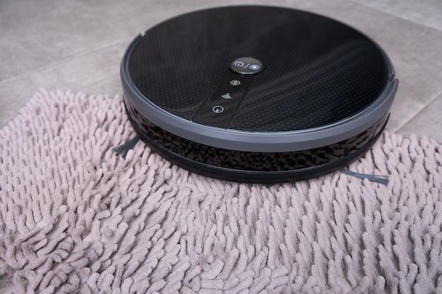 Aspirador de pó robô em um tapete cinza com um grande close-up de pilha.