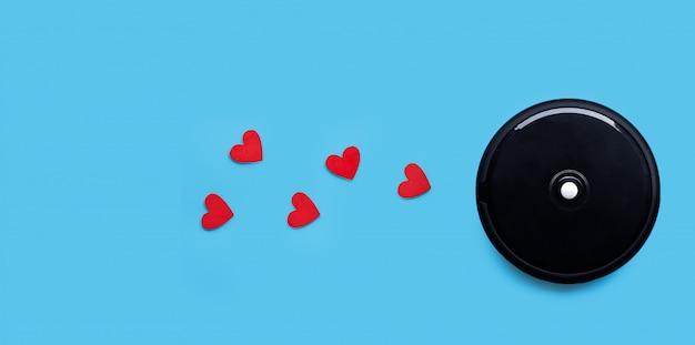 Aspirador de pó robótico com corações vermelhos no fundo azul.