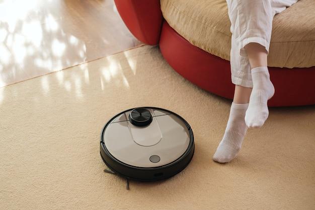 Aspirador de pó robótico e pernas no tapete, aparelhos inteligentes no conceito de casa, conceito de estilo de vida preguiçoso e confortável