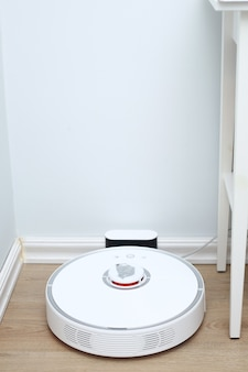 Aspirador de pó robótico em piso de madeira laminado carregando da estação base. tecnologia de limpeza inteligente. o aspirador de pó do robô volta a carregar na doca no piso da sala limpa