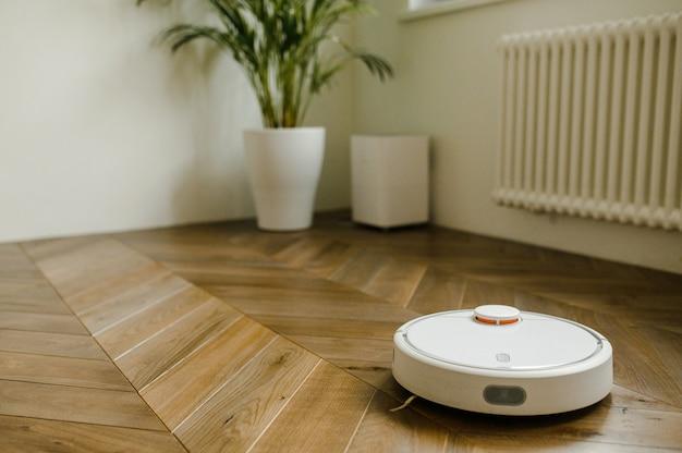 Aspirador de pó robótico no assoalho de madeira laminado no quarto