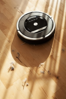 Aspirador de pó robótico no assoalho de madeira laminado