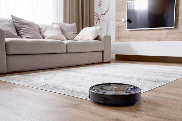 Aspirador de pó robótico no chão na acolhedora sala de estar moderna