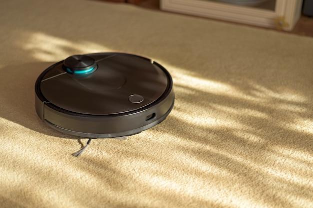 Aspirador de pó robótico preto no tapete, aparelhos inteligentes no conceito de casa