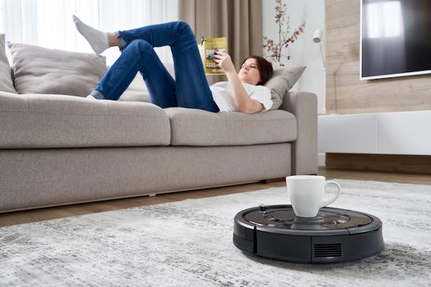 Aspirador de pó robótico trazendo café para uma mulher enquanto ela está descansando no sofá