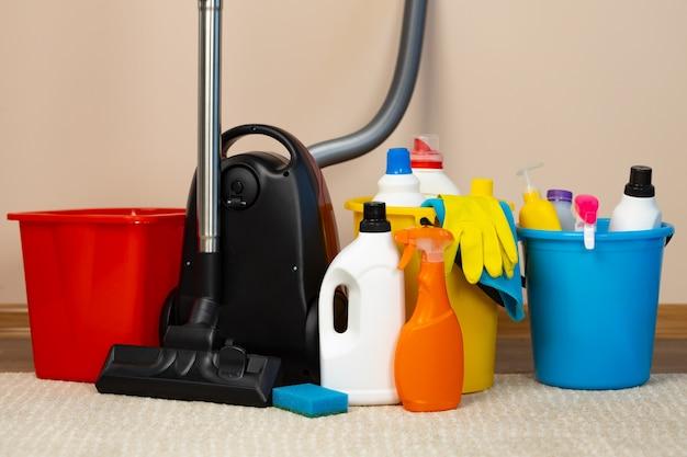 Aspirador de pó vermelho e balde de plástico com detergentes líquidos em carpete bege