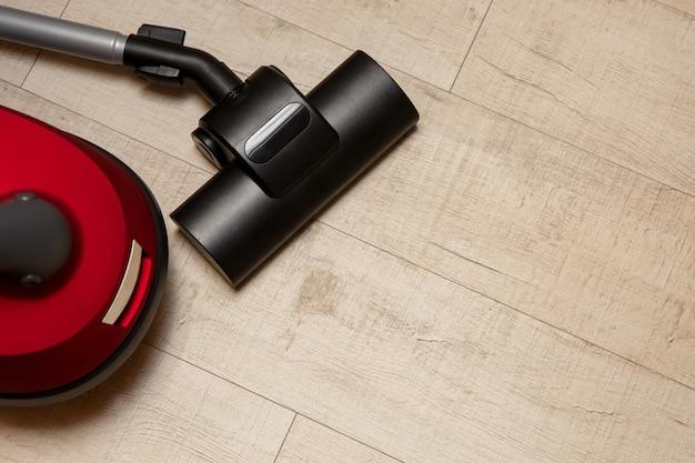 Aspirador no chão, serviço de limpeza, novo aspirador vermelho.