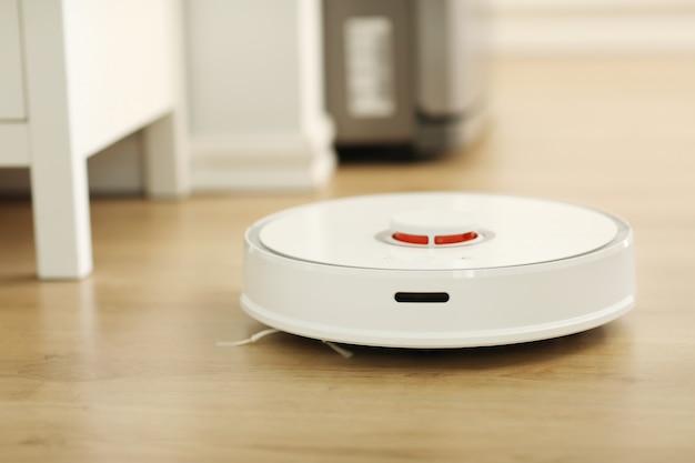 Aspirador robô branco limpa o chão