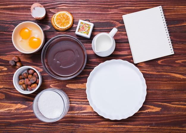 Assadeira branca; gema de ovo; granulados; avelãs; leite; farinha; xarope de chocolate e bloco de notas em espiral no plano de fundo texturizado de madeira