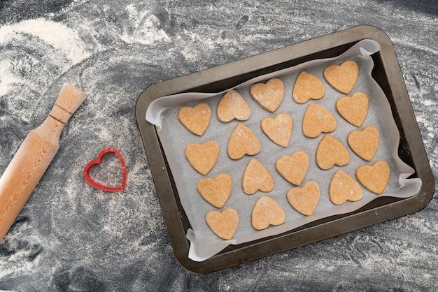 Assadeira com biscoitos em forma de coração e rolo de madeira. cozimento caseiro.