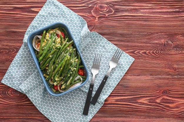 Assadeira com gostosa caçarola de feijão verde na mesa de madeira