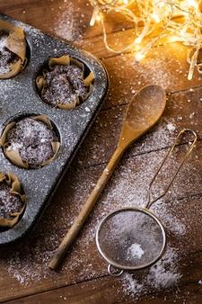 Assadeira com saborosos muffins de chocolate na mesa de madeira