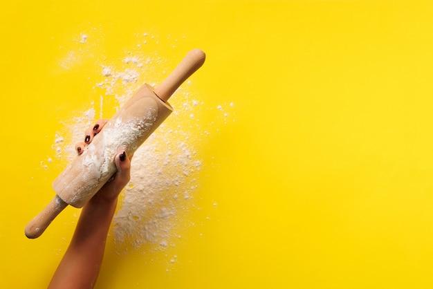 Assadeira plana leigos com rolo, farinha em fundo de papel amarelo.