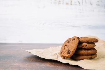 Assado biscoitos de chocolate frescos no papel marrom na mesa de madeira