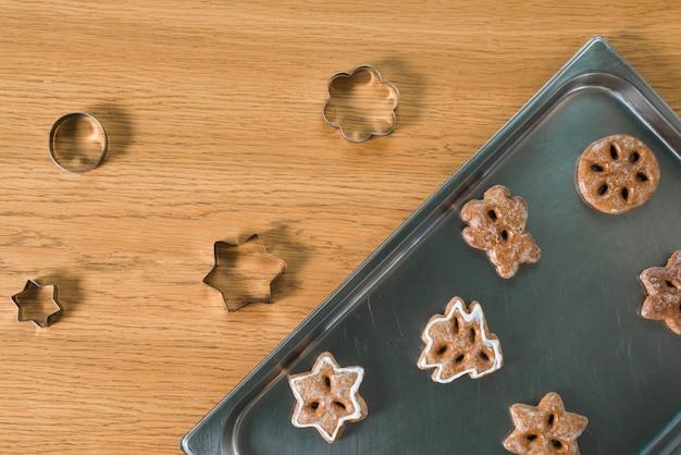 Assado biscoitos de natal e cortadores de pastelaria na mesa de madeira
