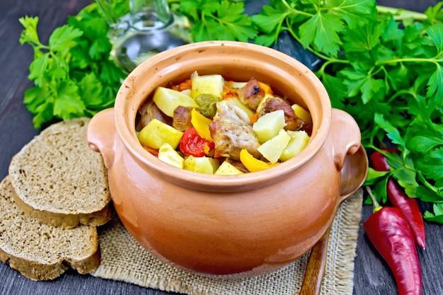 Assado com frango, batata, abóbora e pimentão em uma panela de barro em um guardanapo de serapilheira, colher, pão e salsa sobre um fundo de tábua de madeira